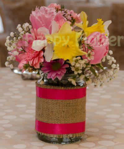 Aranjament de masa in borcan decorat cu floricele de primavara, lalele, narcise, garofite